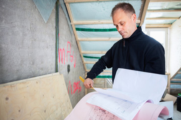 Serious manual worker reading blue prints while standing at construction site