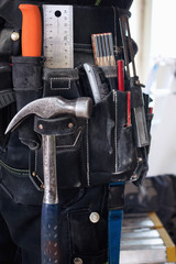 Midsection of construction worker wearing tool belt