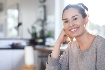 Portrait of happy woman sitting in kitchen at new home