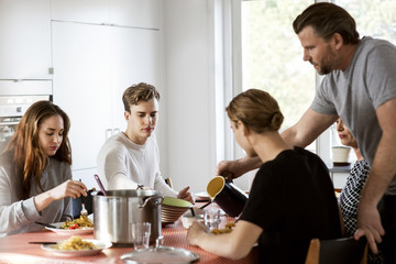 Man serving water for family at dining table at new house