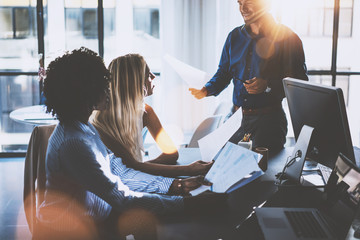 Young team of coworkers making great meeting discussion in modern coworking office.Hispanic businessman talking with two beautiful womans.Teamwork process.Horizontal,blurred background,sun effect.
