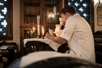 Master Balsamic maker testing quality of the condiment in traditional way with candle