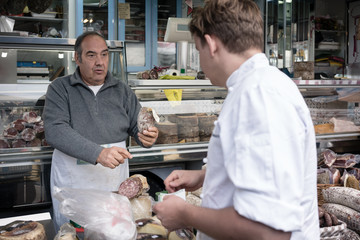 Seller man at farmers market offering samples of food to chef cu