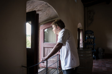 Winegrower looking out of window in winery