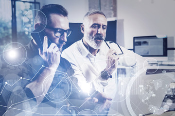 Concept of digital screen,virtual connection icon,diagram, graph interfaces.Bearded young man using mobile phone and adult colleague looking to laptop for find great work solution.Film effect,flare.