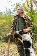 Man and his dog on truffle hunt in woods of Tuscany, Siena, Ital