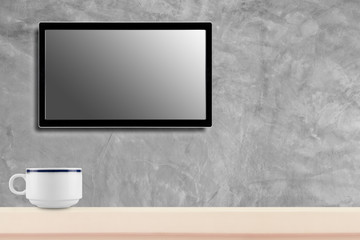 LED television screen mockup, blank hdtv on concrete wall with coffee cup in the room