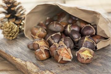 Frisch geröstete Maroni aus der Markttüte auf rustikalem Holz