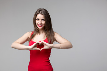 Beautiful woman making a heart symbol with her hands