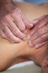 Woman receiving shoulder massage from physiotherapist