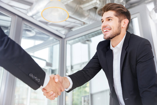 Two successful businessmen shaking hands on business meeting in