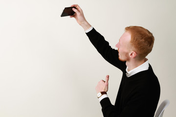 Businessman with mobile phone. Ginger  a successful man with a beard. Taking photo.