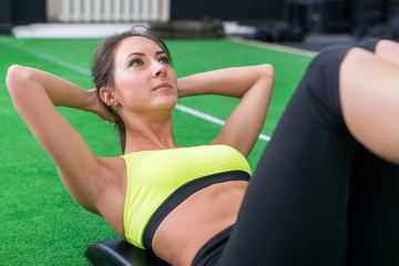 portrait of an athletic woman doing exercising abdominals work-out lying in gym