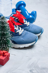 Christmas sport composition with sport shoes, dumbbells, gift