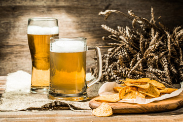 Mug, glass of beer on cloth with spikelets and chips
