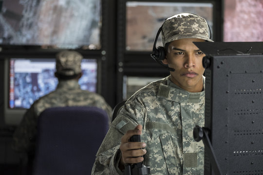 Military drone operator looking at computer screen