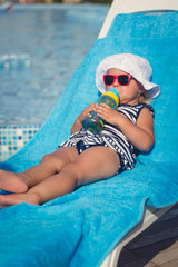Portrait of baby drinking water on sunbed near swimming pool