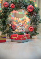 Christmas gifts. Snowman figurine.Blurry Christmas lights out of focus in the background.