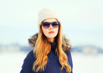 Fashion winter portrait pretty blonde woman wearing a jacket hat