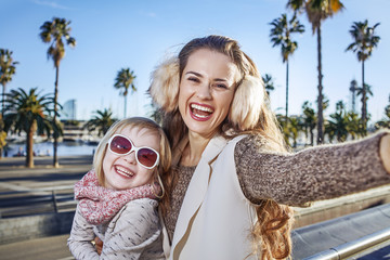 mother and daughter on embankment in Barcelona taking selfie