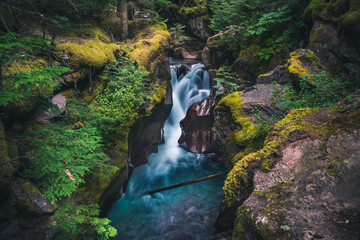 Fototapete - Lush waterfall flowing over boulders. Glacier National Park, Montana, USA