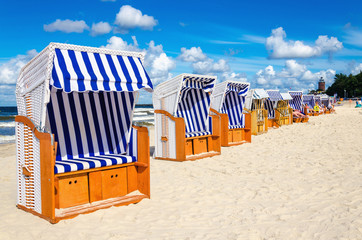 Blue and white wicker chairs on sandy beach