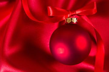 Red christmas ball on a silk cloth