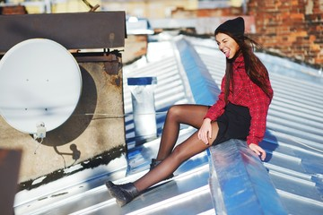 Cheerful long-haired girl sitting on an iron roof in windy and Sunny day on background of brick wall and laughs, making faces and showing language, side view.