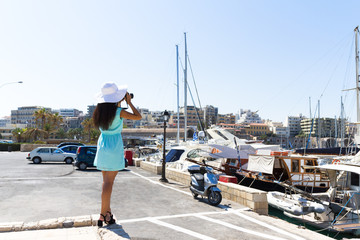 Young stylish woman photographing the venetian port Heraklion, C