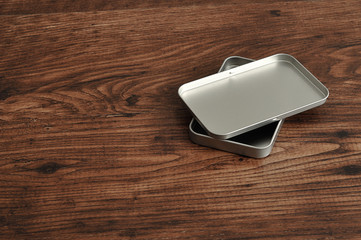 A small empty metal tin with a lid