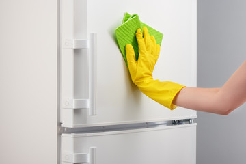 Hand in yellow glove cleaning white refrigerator with green rag