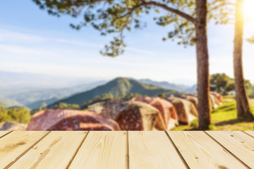 Wooden board empty table in front of blurred background of  tent for camping in the mountain with pine trees and sea of fog and flare used for mock up for display or montage your products, vintage.
