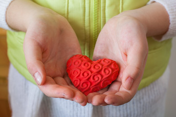 young girl holds in her hands handmade gift heart