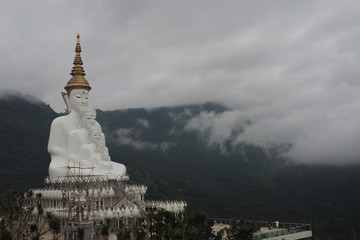 white  statue with clouds.