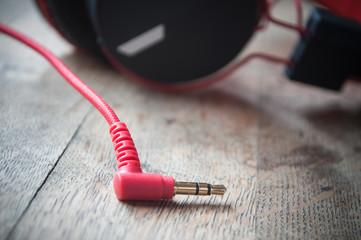 détail prise jack et casque audio rouge et noir sur table en vieux bois