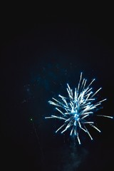 Shiny natural fireworks on dark black sky background with a litt