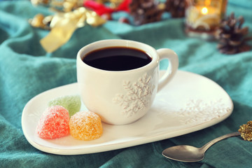 Cup of coffee and pine cones, burning candle and colorful candy