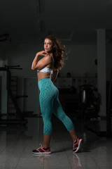 Fitness Shaped Muscle Woman Posing In Dark Gym