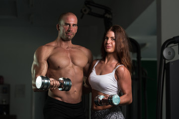 Young Couple Doing Heavy Weight Exercise For Biceps