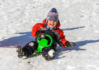 Little boy enjoying a sleigh ride. Children play outdoors in sno
