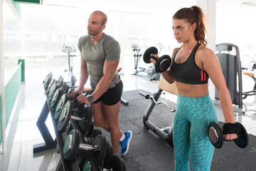 Couple With Dumbbells Exercising For Biceps