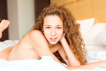 Young natural woman lying on her bed with little clothes