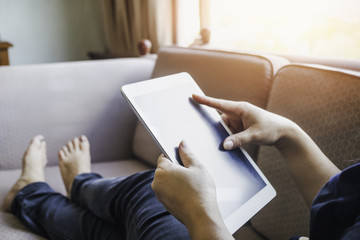 Woman using tablet at home, lying on the sofa
