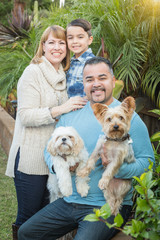 Happy Mixed Race Family Portrait Outdoors with Their Dogs.