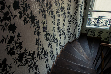 Narrow wooden staircase with busy wallpaper and window