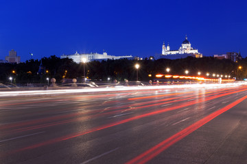 Traffic at night in Madrid on the Segovia bridge with the Almudena Cathedral and Royal Palace in the background