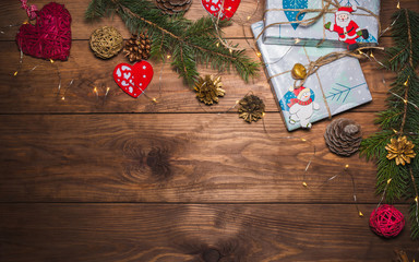 Christmas presents in gift boxes at brown wooden table. Flat lay with copy space Christmas decorations and objects Christmas fir tree branches, hearts, cones. garland Free space