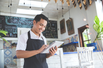 young male cafe owner with tablet