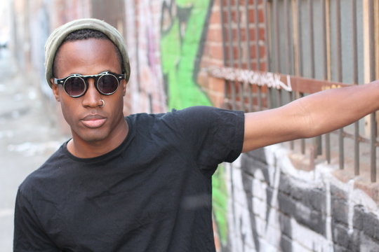Fashion african man wearing a sunglasses, beanie, piercing and black tee over urban background in city alley