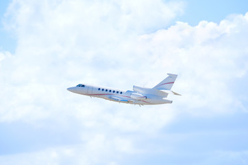 A clean white private business jet airliner plane in flight climbing in altitude with beautiful fluffy clouds and blue sky in the background